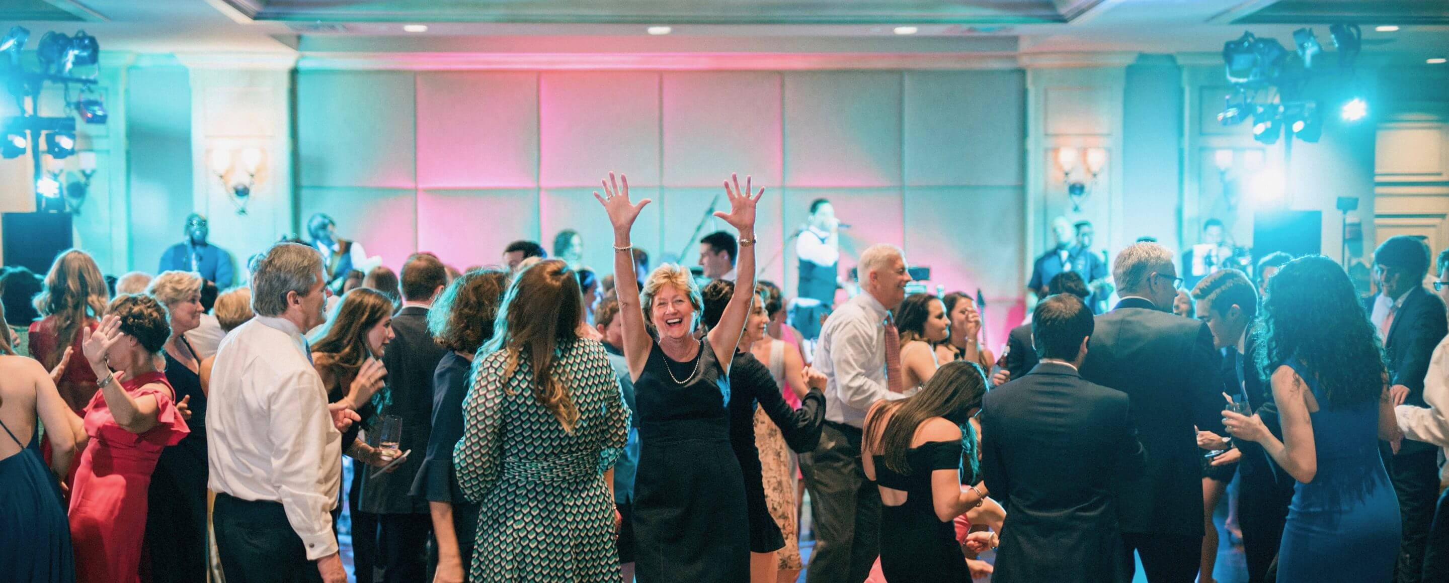 Attendees dancing at wedding reception hosted by band None Other