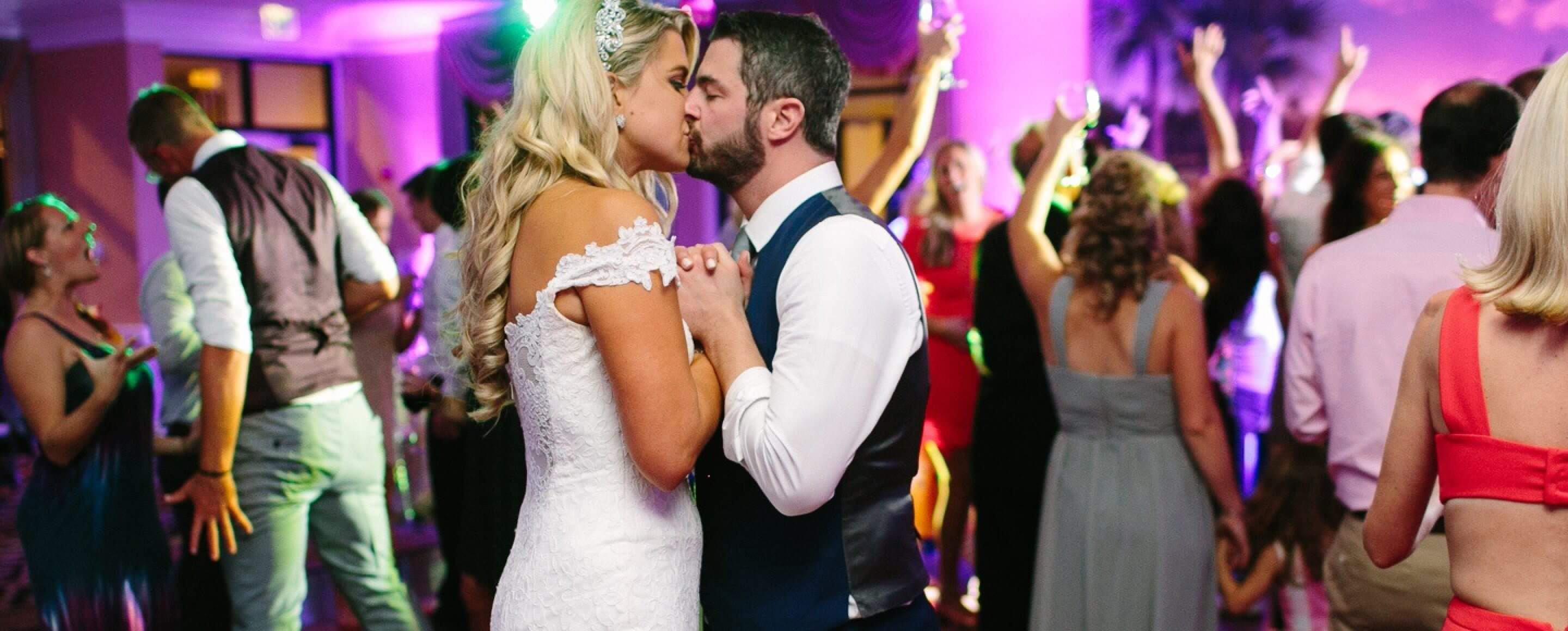 Bride and groom kissing at their wedding reception hosted by band None Other